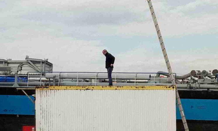 Mann auf Container kommt